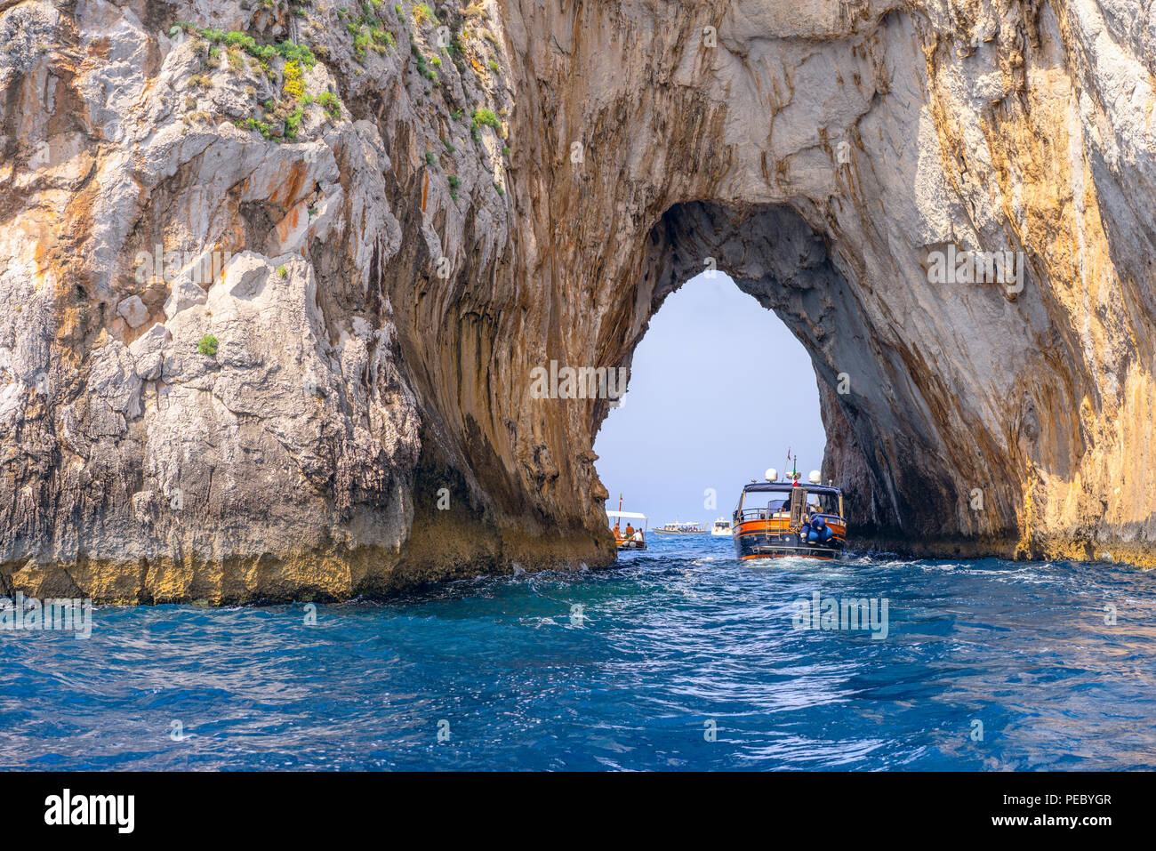 Sailing through the Faraglioni by boat these are stacks which are formed from rocks on the southern side of Capri - Stock Image