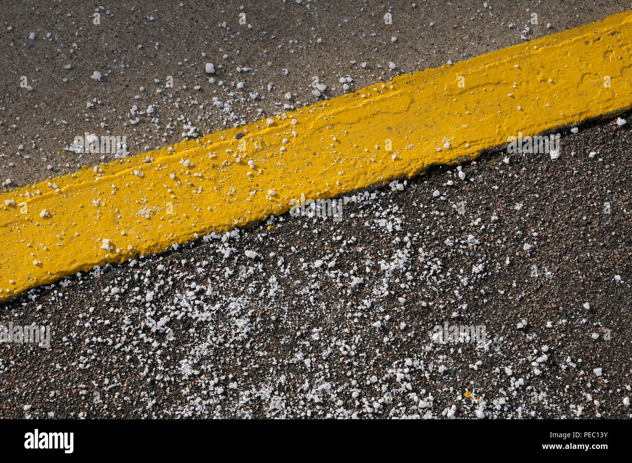 Road salt grit / rock salt / sodium chloride scattered around a painted yellow line - Stock Image