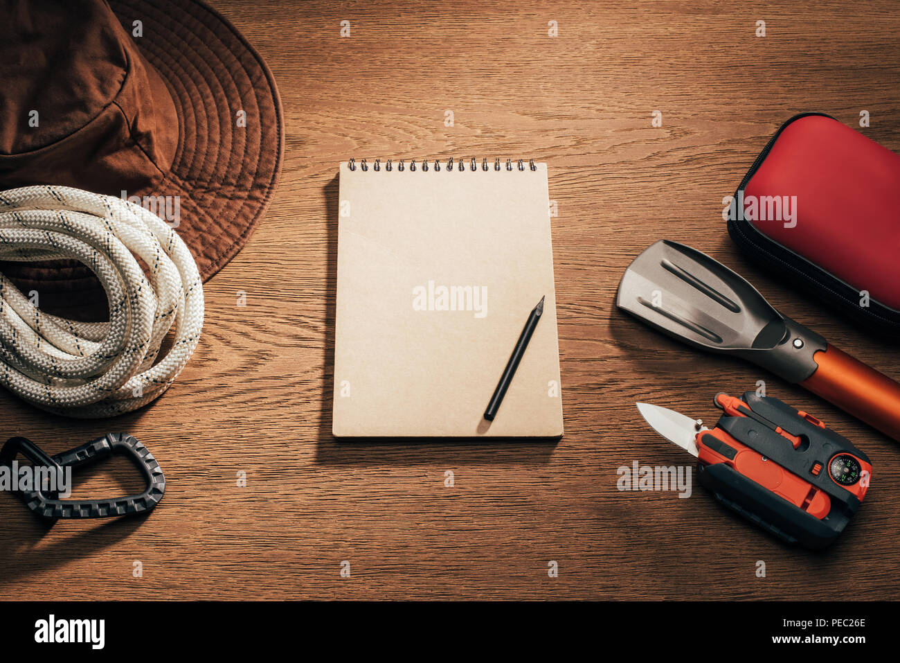 top view of blank notepad with pencil and trekking and hiking items on wooden table - Stock Image