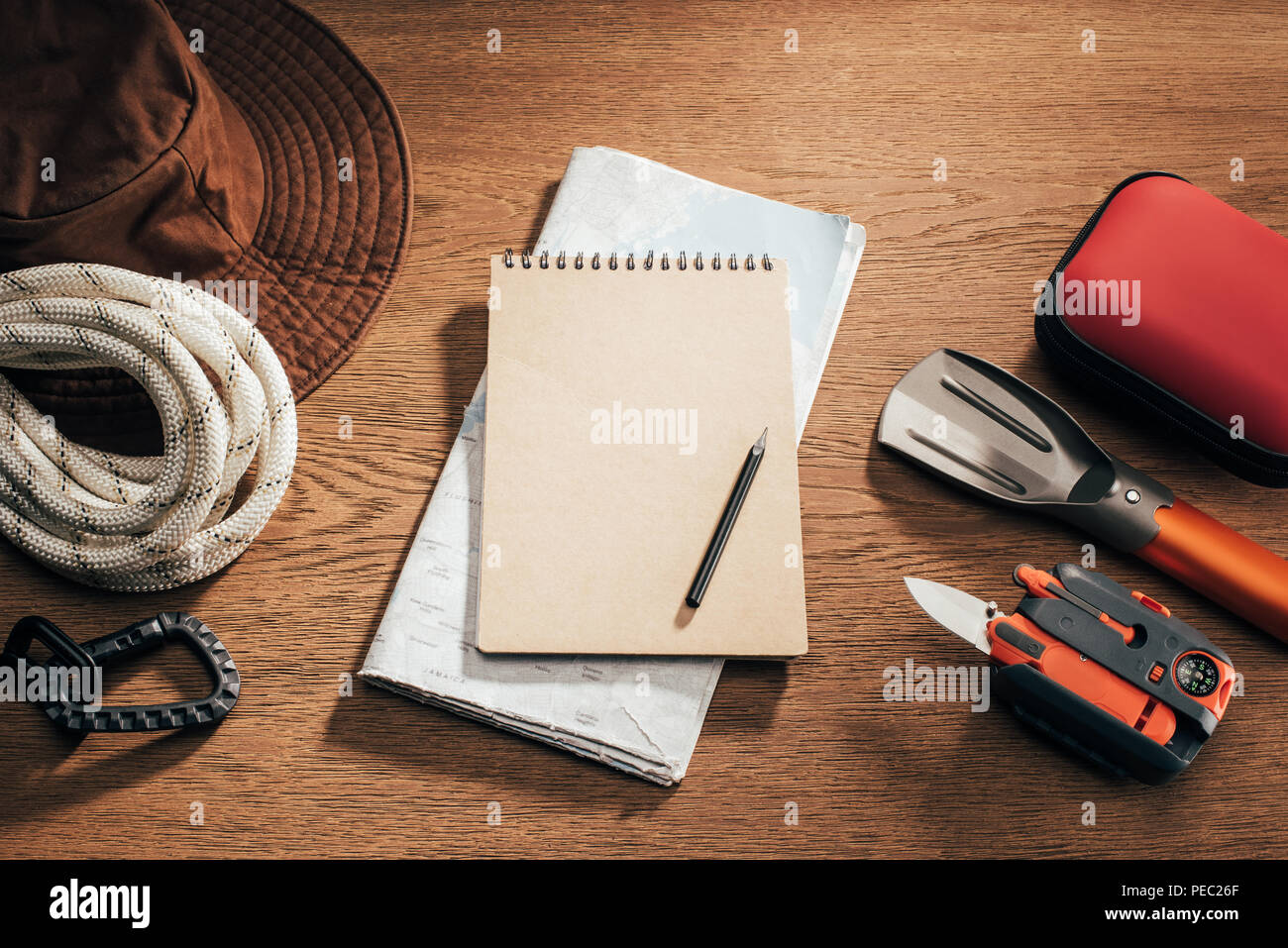 top view of blank notebook with pencil, map and travel items on wooden table - Stock Image