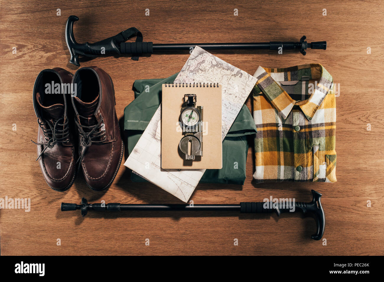 flat lay with trekking sticks, compass, map and clothes with footwear on wooden table - Stock Image