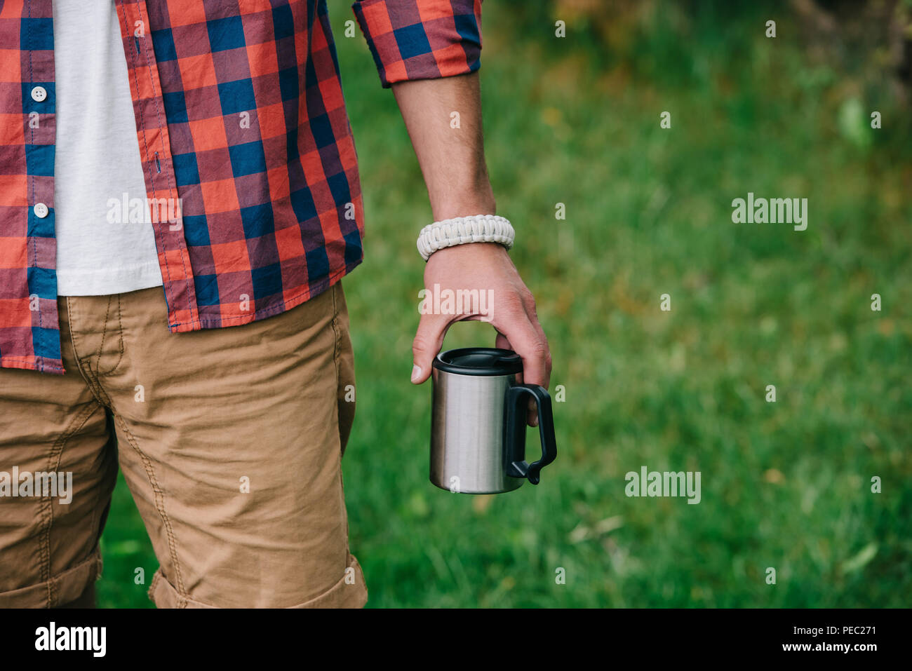 partial view of man in checkered shirt holding mug outdoors - Stock Image
