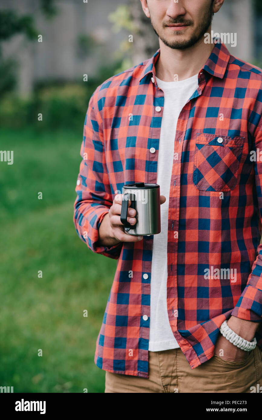 cropped shot of young man in checkered shirt holding mug - Stock Image
