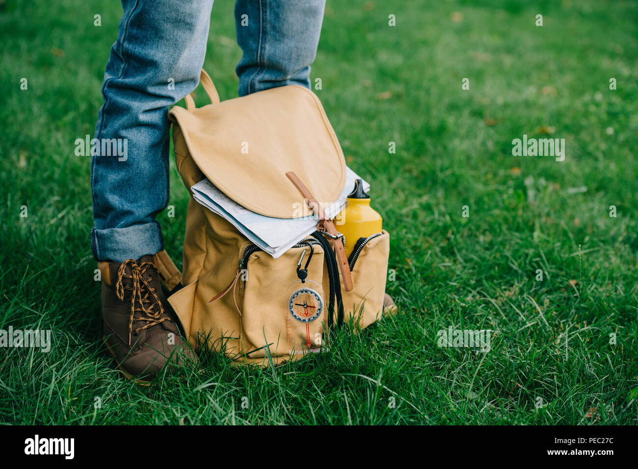 cropped shot of man standing on green grass with backpack Stock Photo