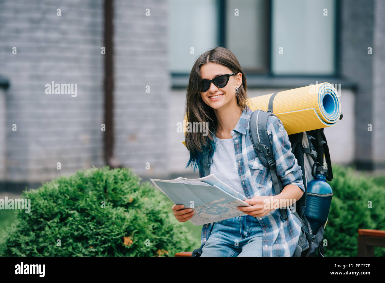 happy young woman with backpack holding map and smiling at camera - Stock Image