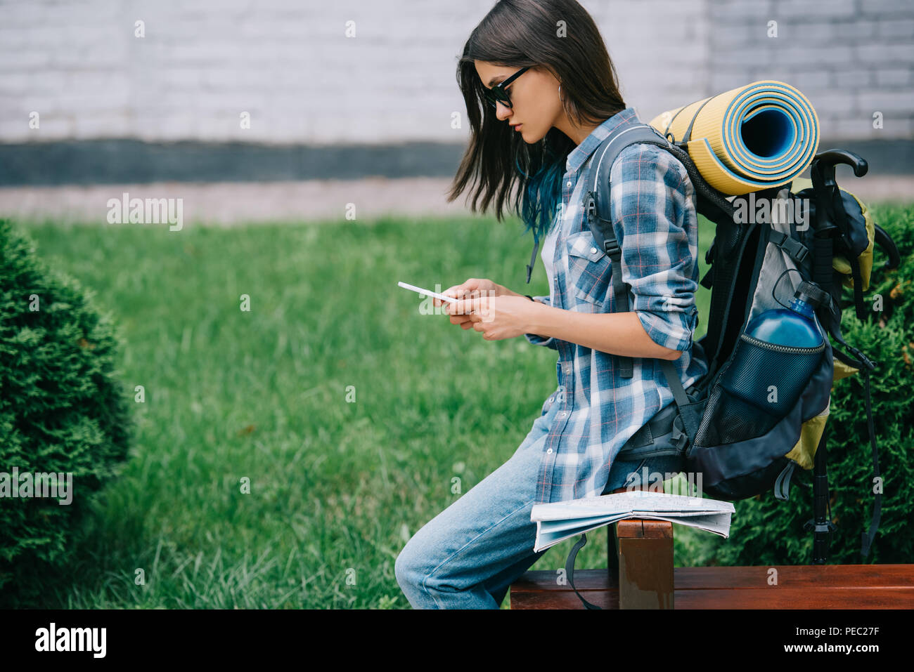 side view of beautiful young woman with backpack using smartphone - Stock Image