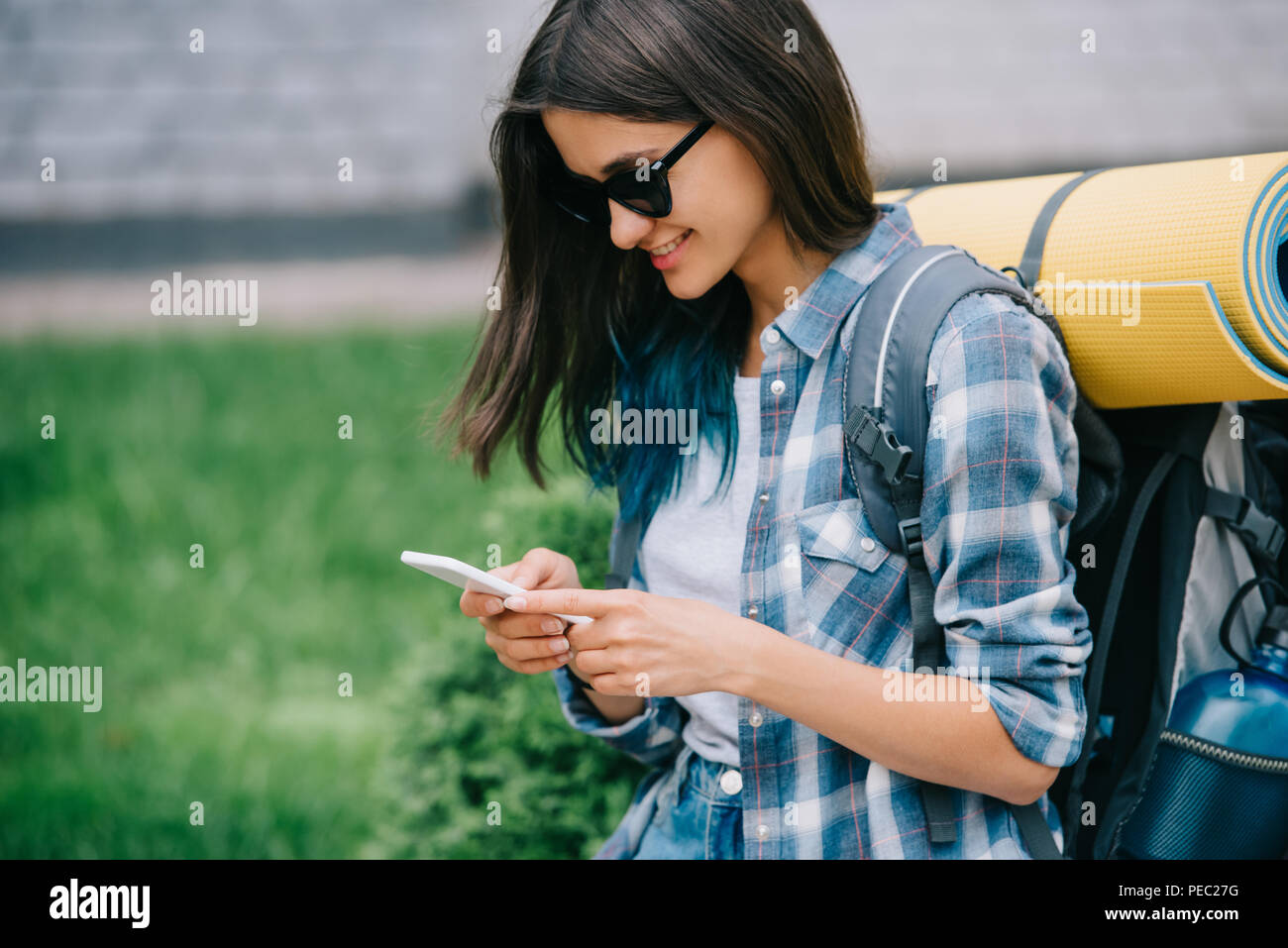 smiling young woman with backpack using smartphone - Stock Image