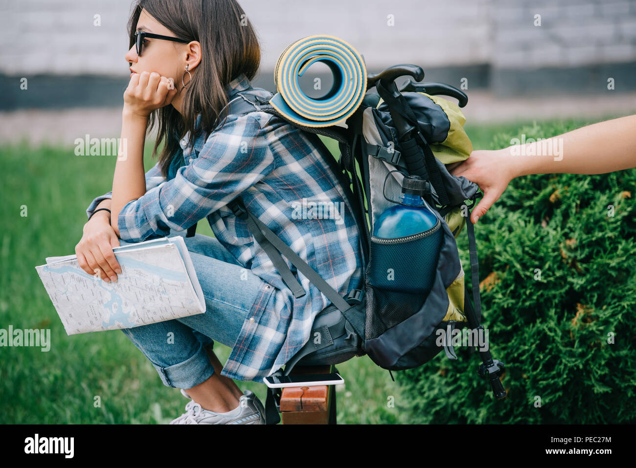 side view of girl traveler holding map and looking away while someone stealing from backpack - Stock Image