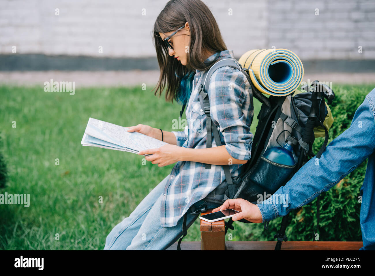 side view of girl traveler holding map while thief stealing smartphone - Stock Image