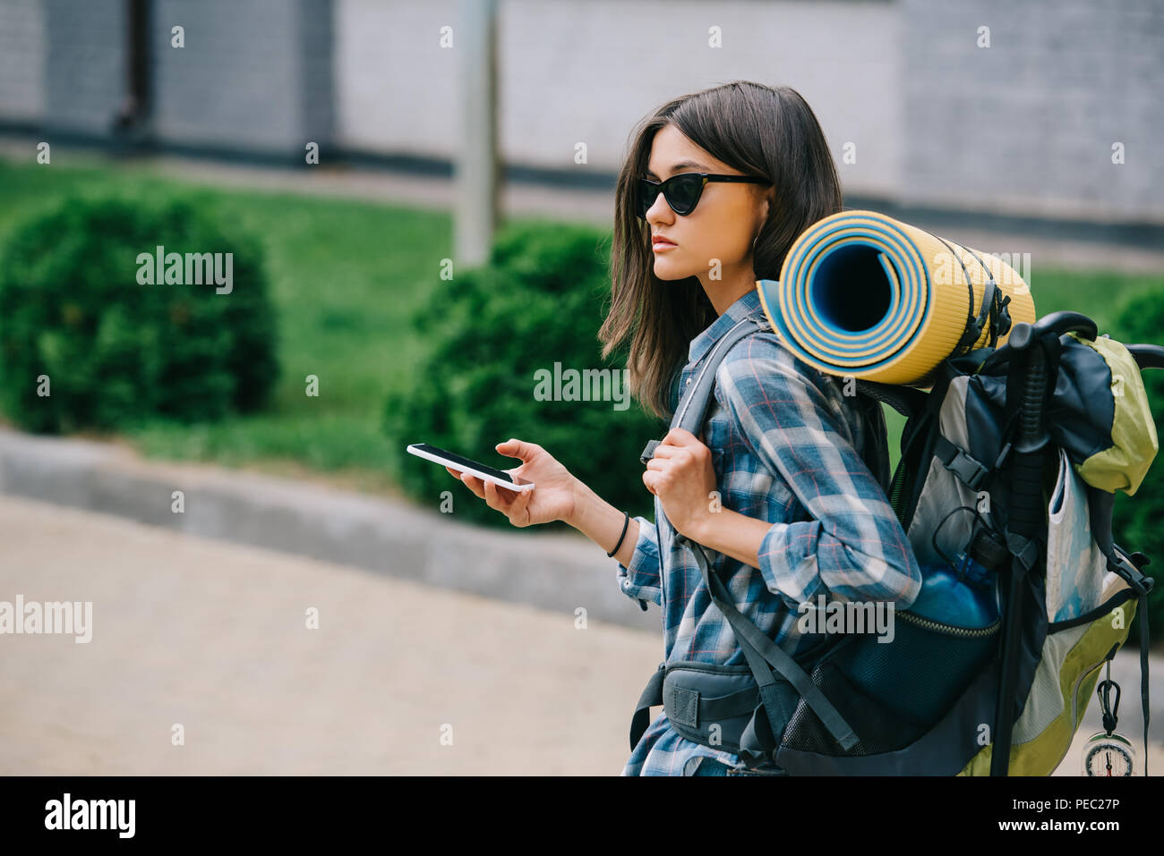 young female backpacker in sunglasses holding smartphone - Stock Image