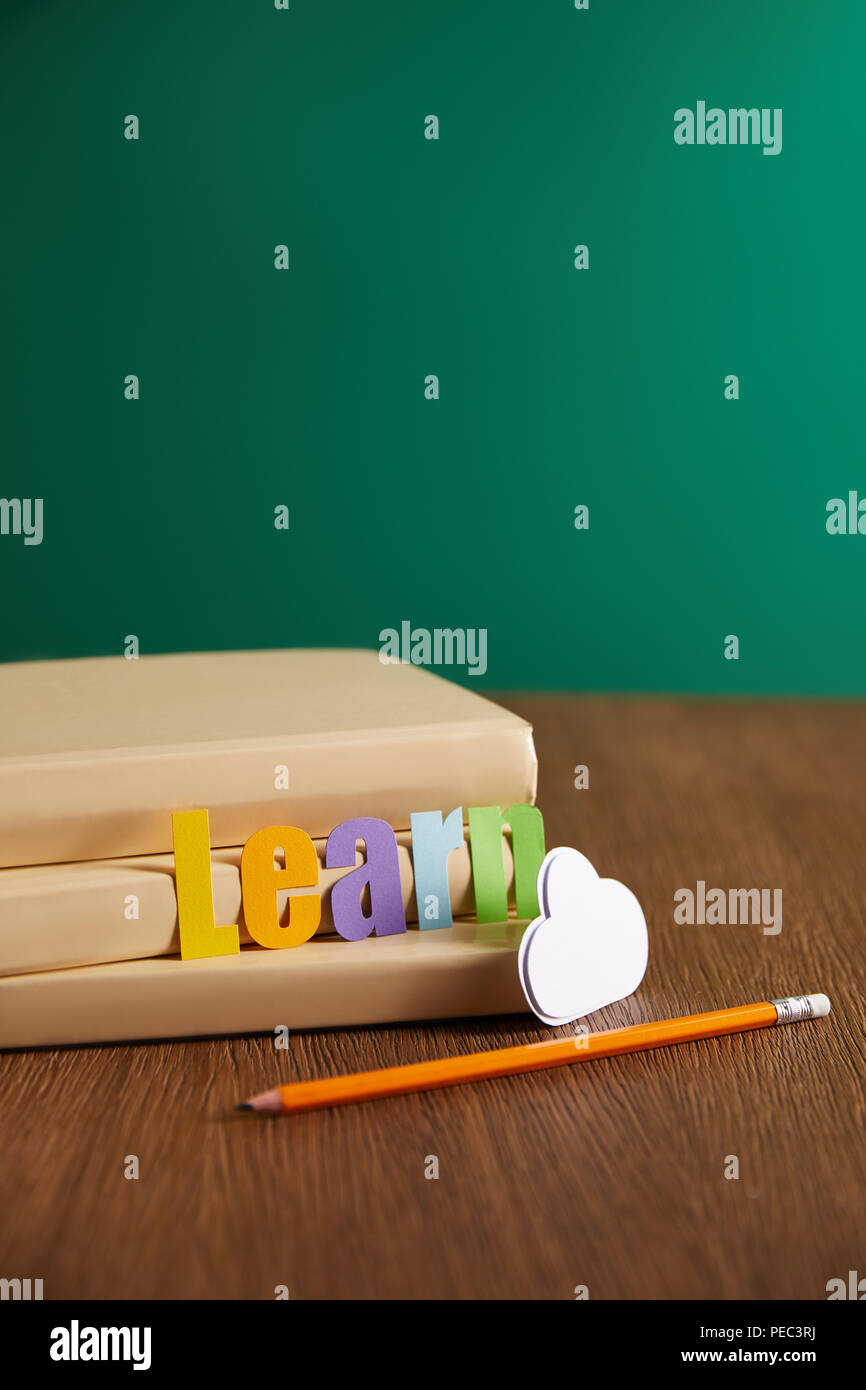 Books Pencil Cloud Sign And Learn Lettering On Wooden Table Stock