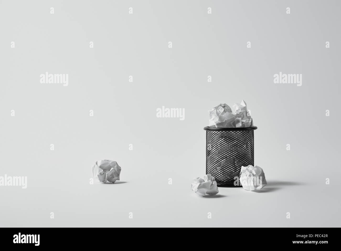 office trash can with crumpled papers on white surface - Stock Image