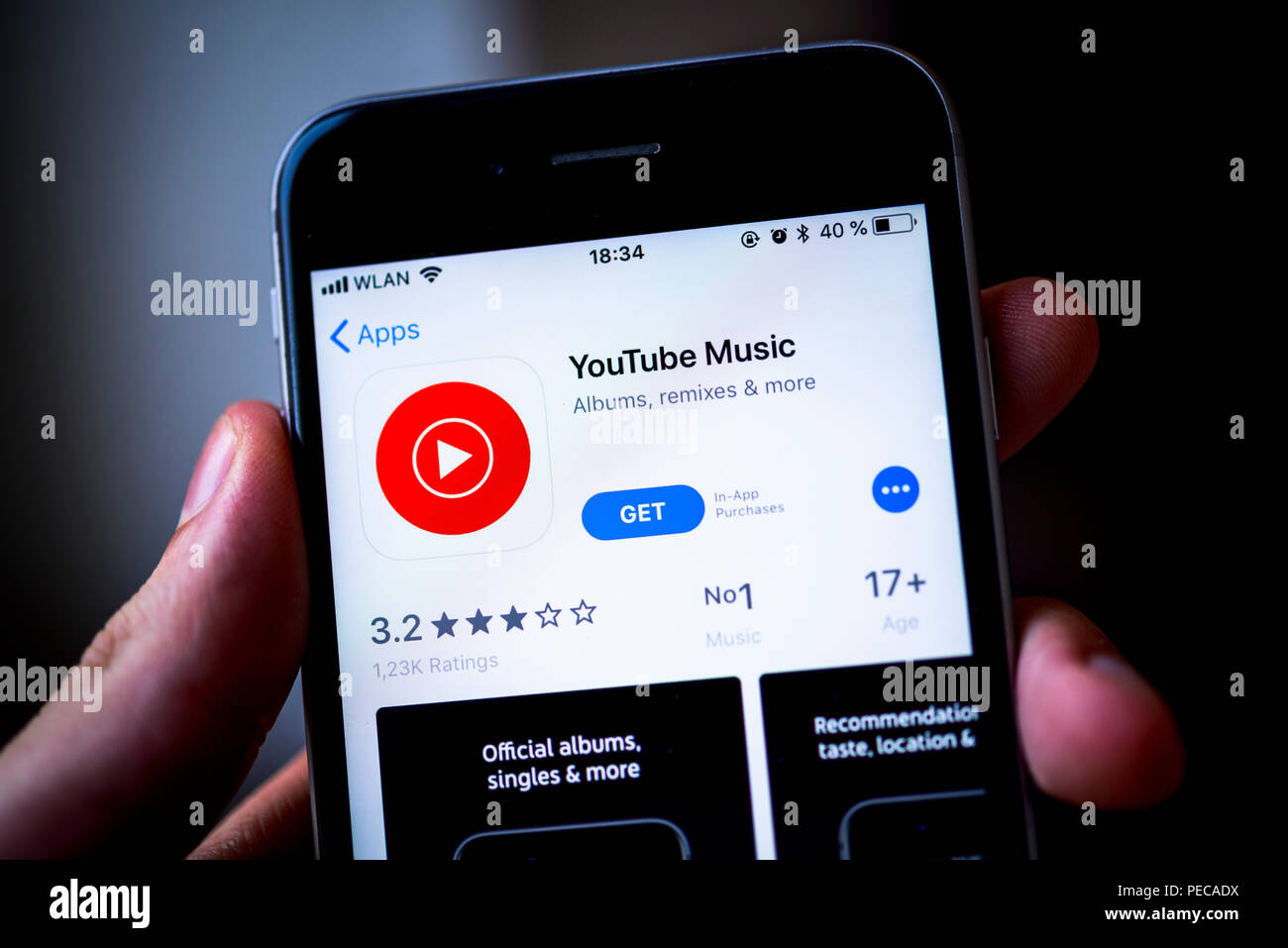 Hand holding iPhone with YouTube Music App in the Apple App Store