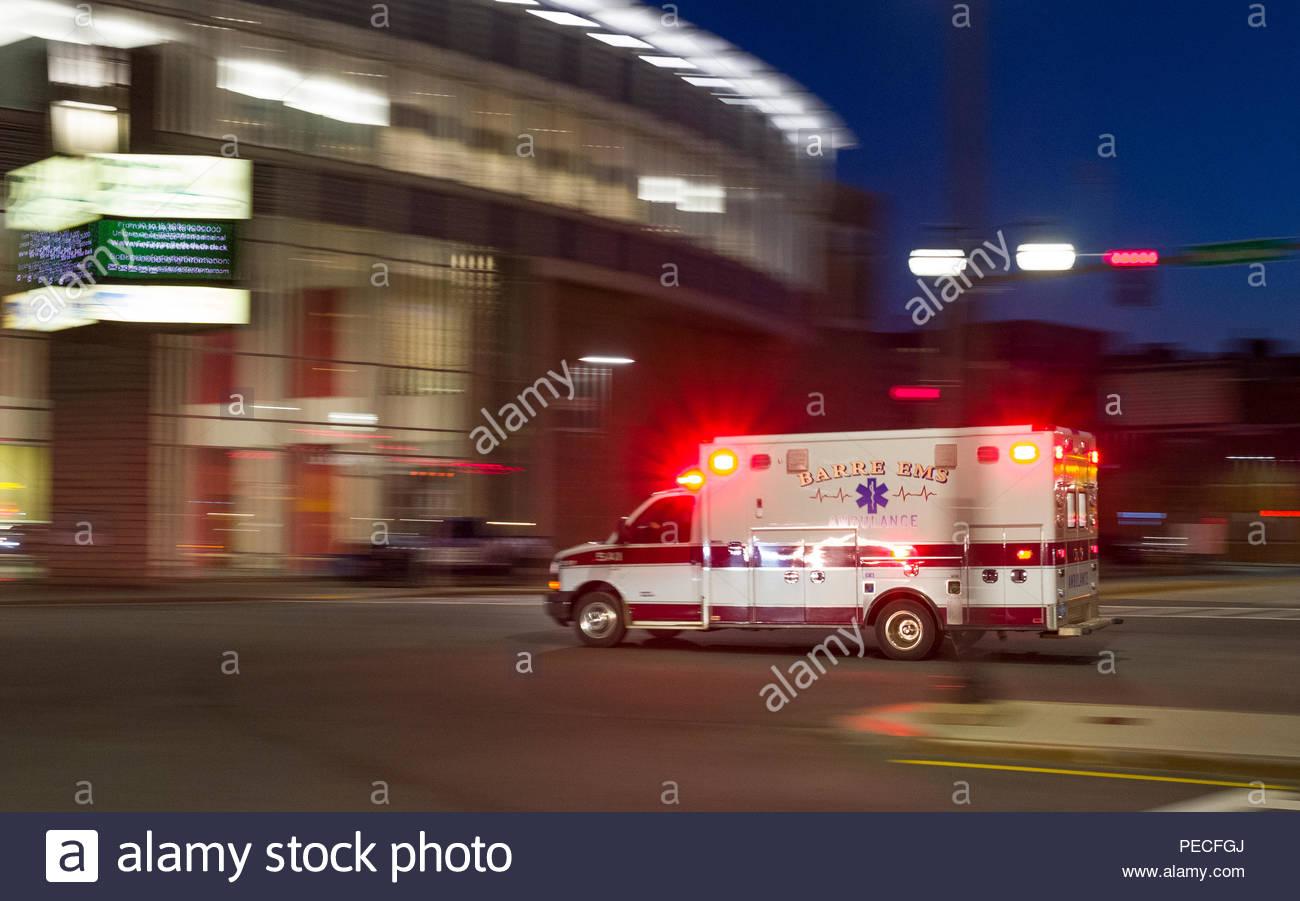 Barre EMS ambulance speeding down road with emergency strobe lights flashing, Worcester, Massachusetts, USA Stock Photo