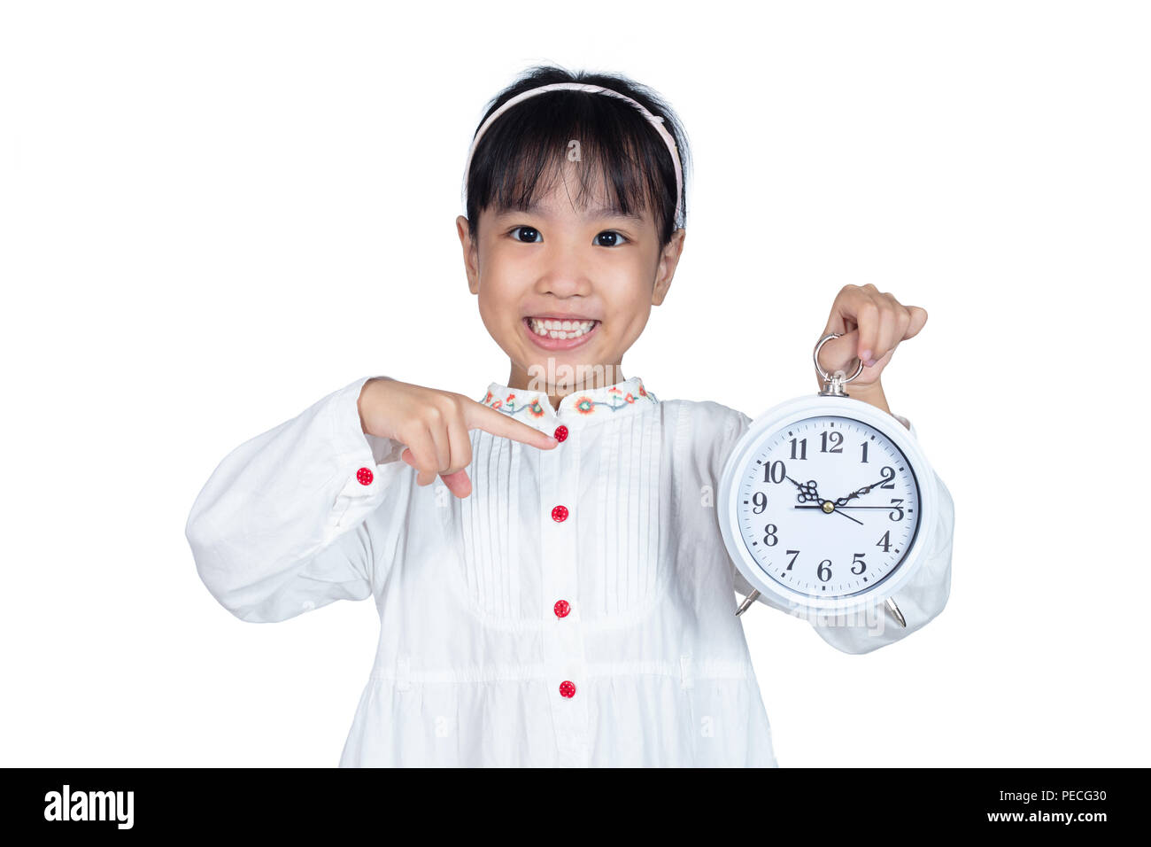 Asian Chinese Little Girl holding alarm clock in isolated white background - Stock Image