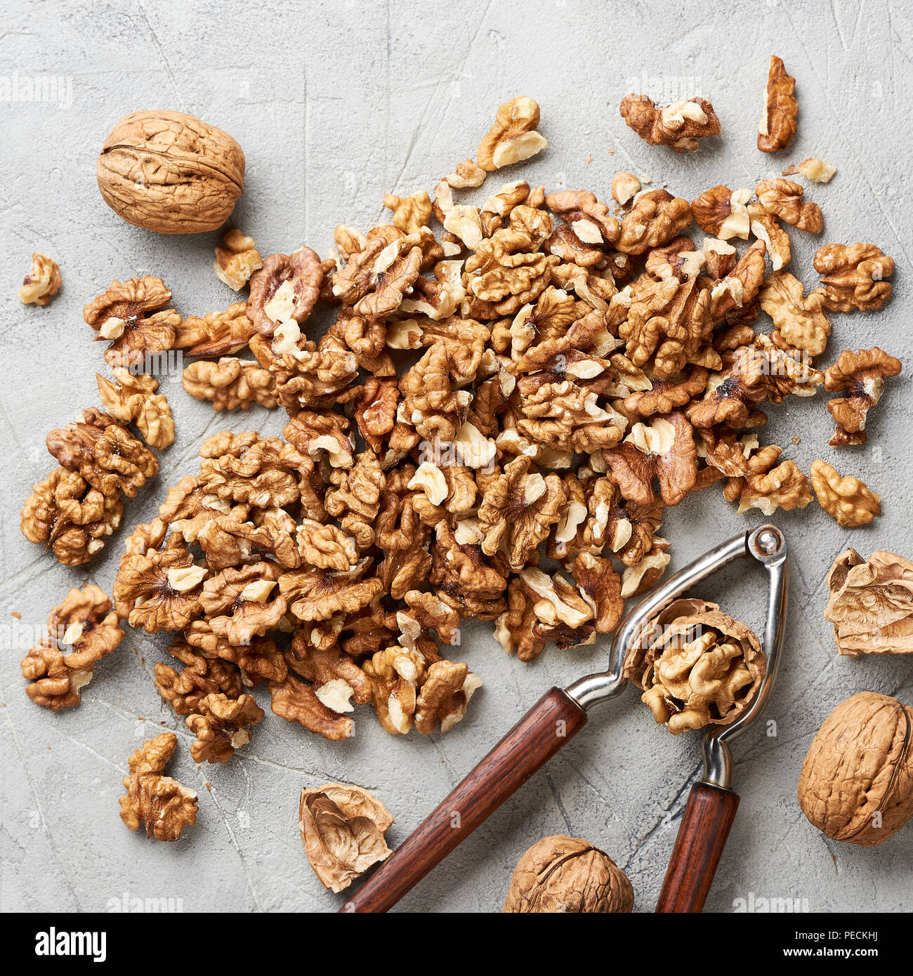 Walnut kernels on gray background and nutcracker. - Stock Image