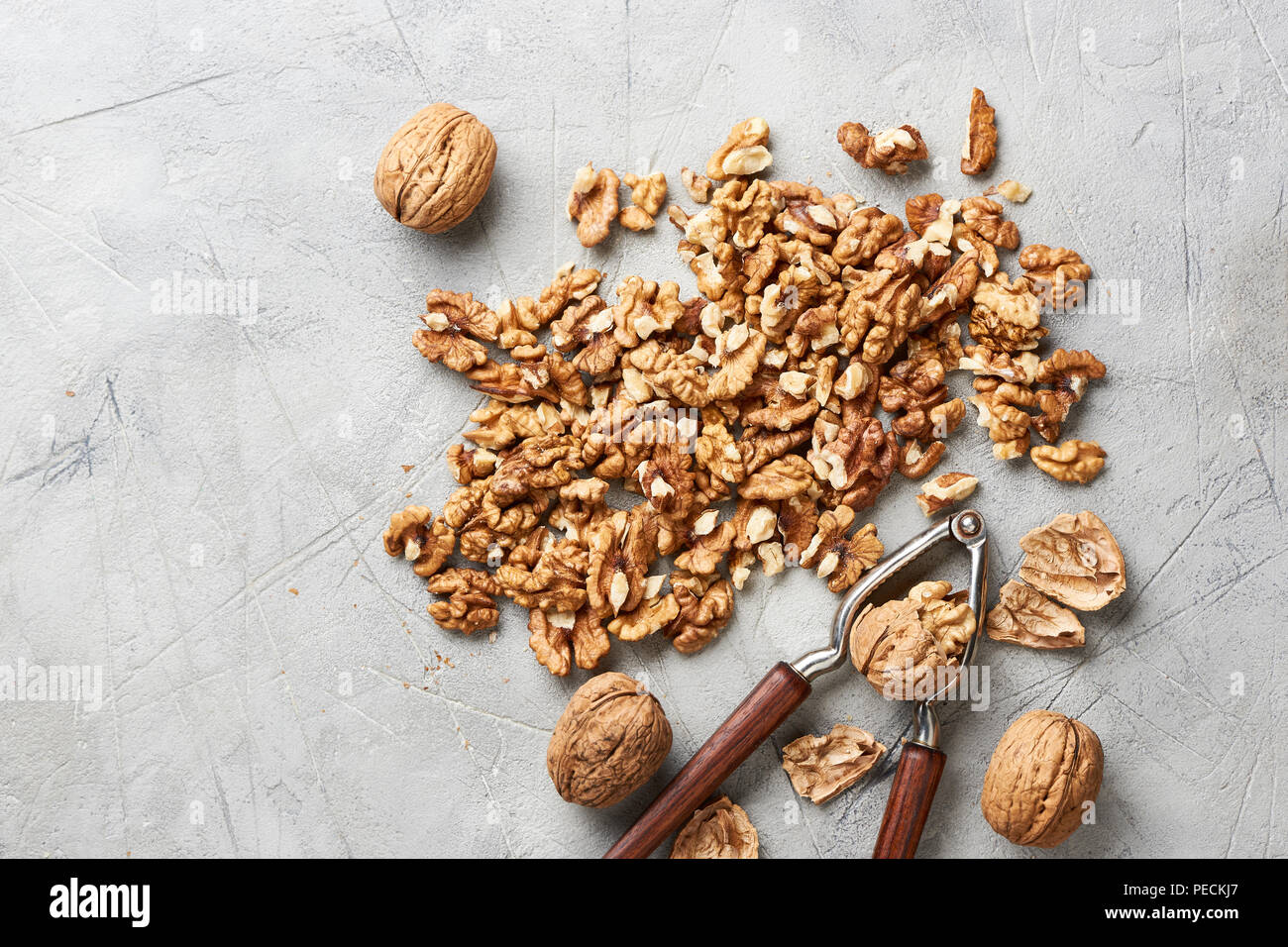 Walnut kernels on gray background with nutcracker. - Stock Image