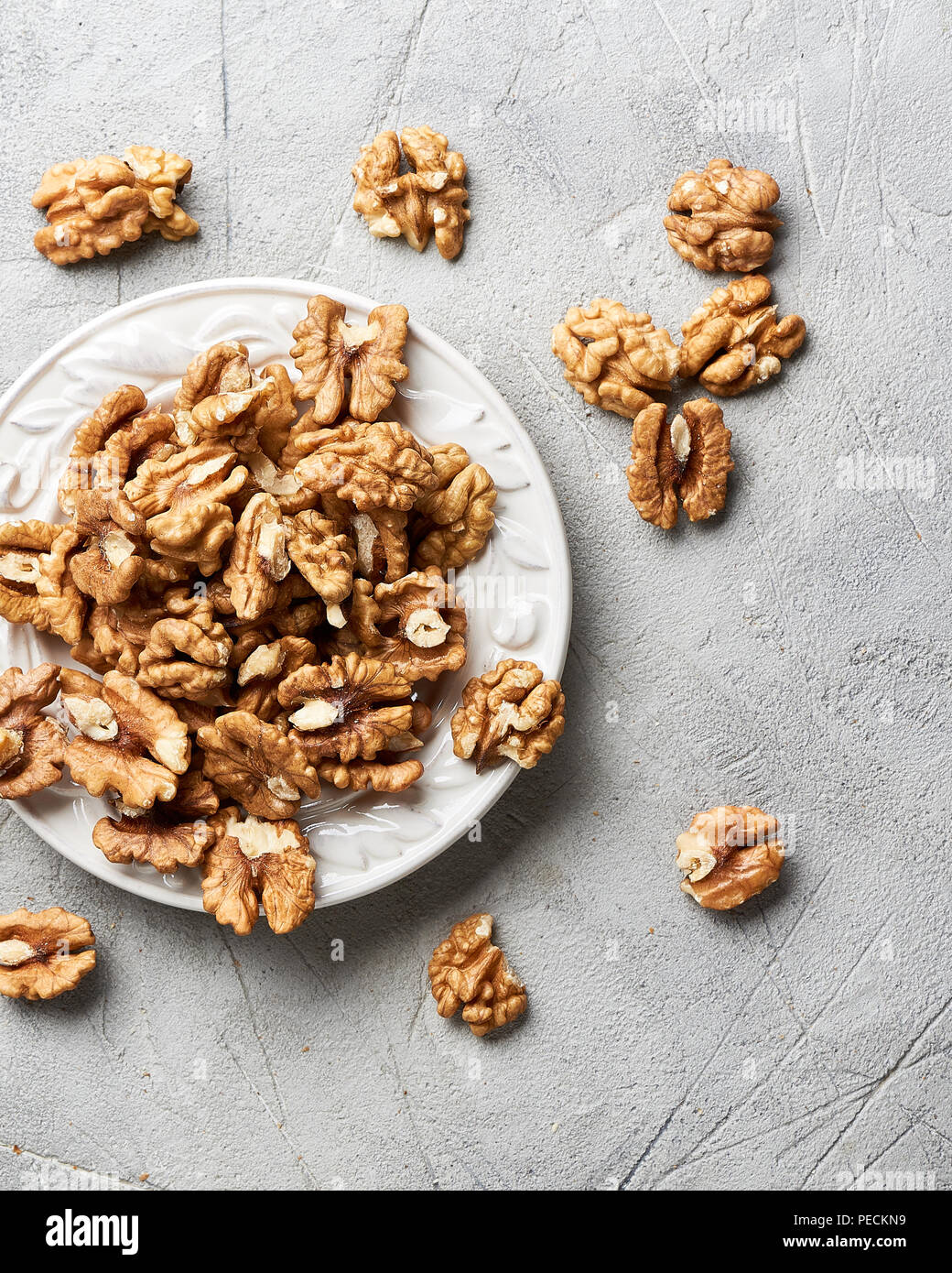 Walnut kernels on white plate over gray background. - Stock Image