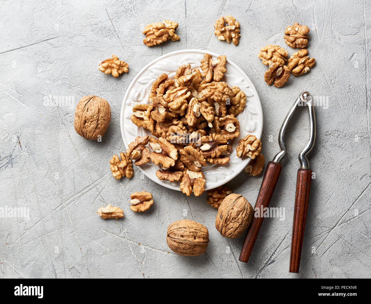 Walnut kernels on white plate over gray background with nutcracker. - Stock Image