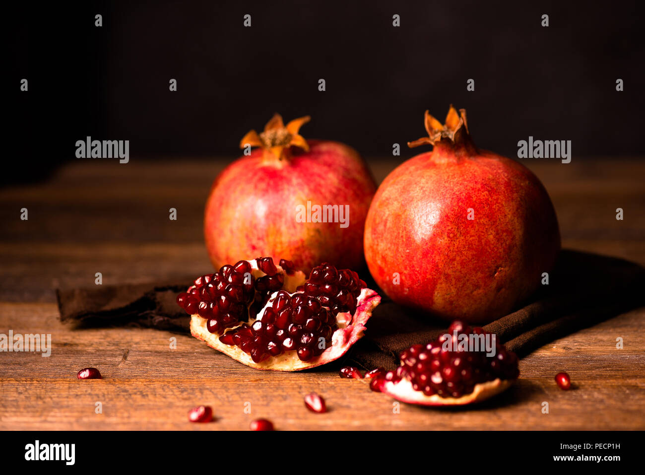 Pomegranate fruits with grains on wooden table. Dark moody. Life style. - Stock Image