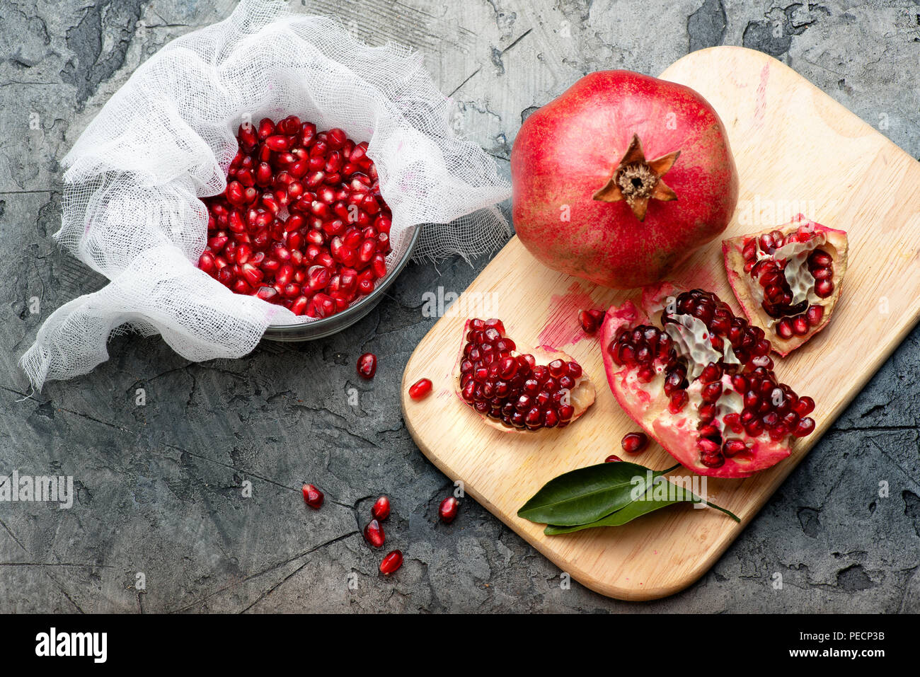 Pomegranate fruits with grains and leaves on the table. Top view. Make juice. - Stock Image