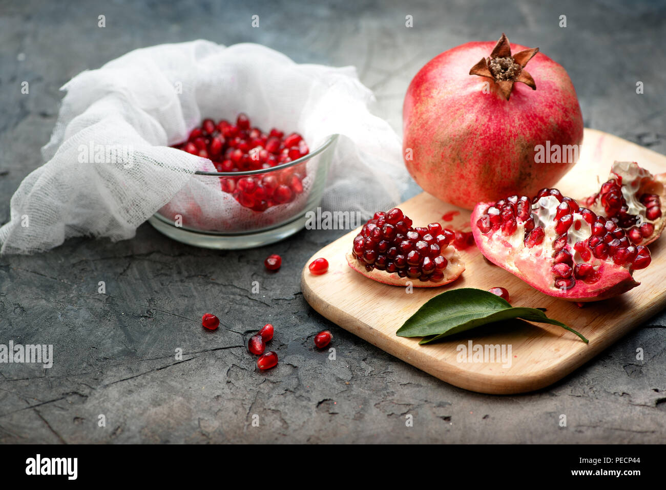 Pomegranate fruits with grains and leaves on the table. Make juice. - Stock Image
