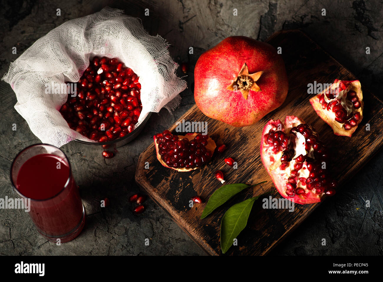 Pomegranate fruits with grains and leaves on the table. Make juice. Top view. Dark moody. - Stock Image