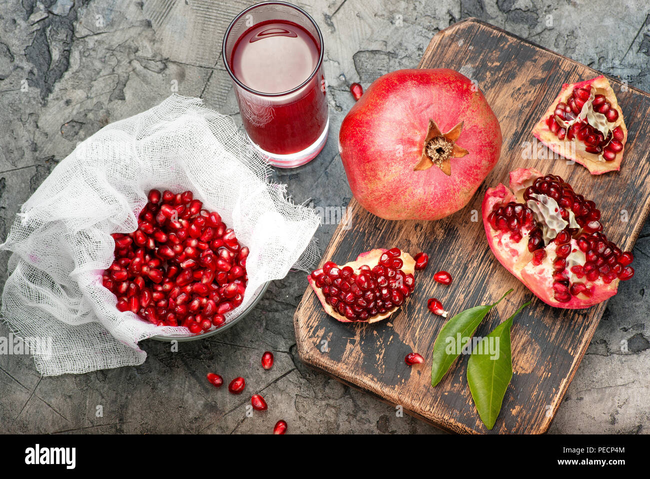 Pomegranate fruits with grains and leaves on the table. Make juice. Top view. - Stock Image