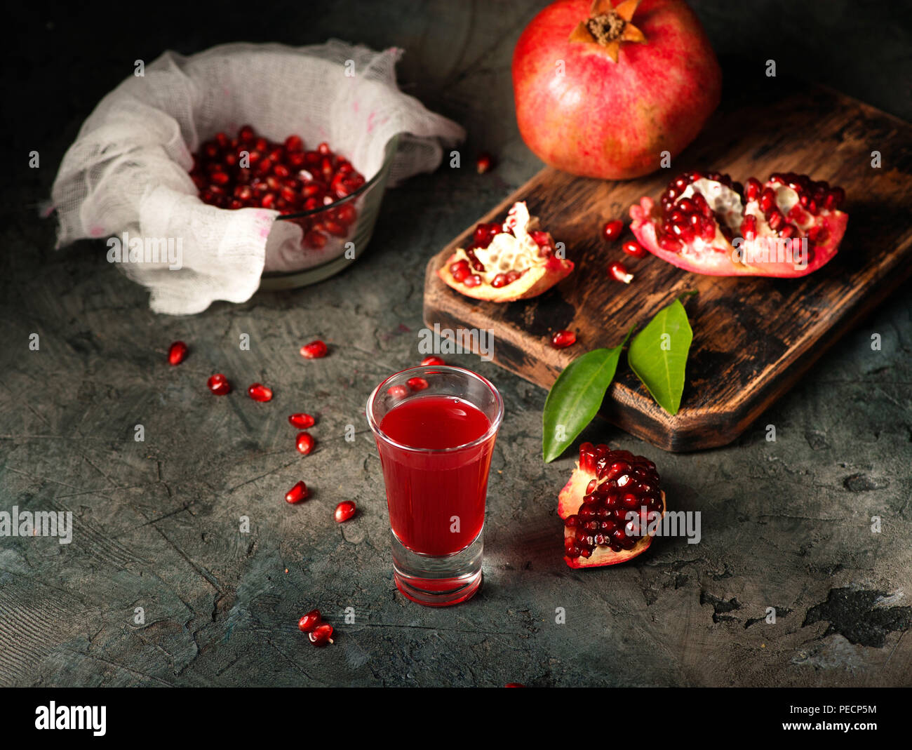 Glass of pomegranate juice. fruits with grains and leaves on the table. Make . Dark moody. - Stock Image