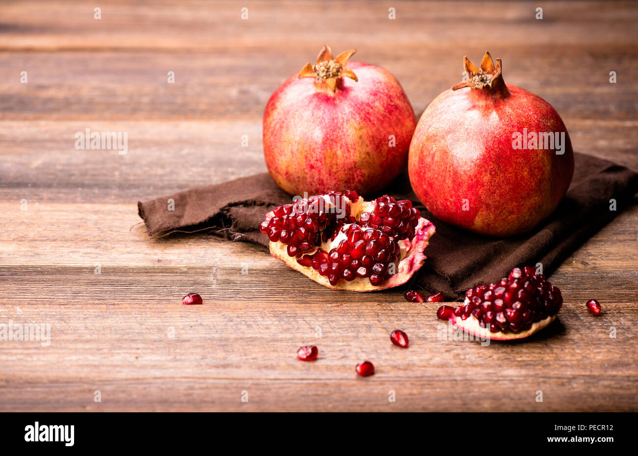 Pomegranate fruits with grains on wooden table. - Stock Image
