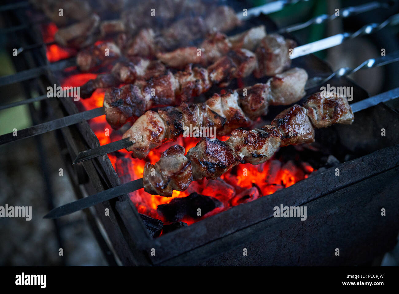Shashlik preparing on a barbecue grill over charcoal. Pieces of meat on skewers. Shish kebab prepare on fire. - Stock Image