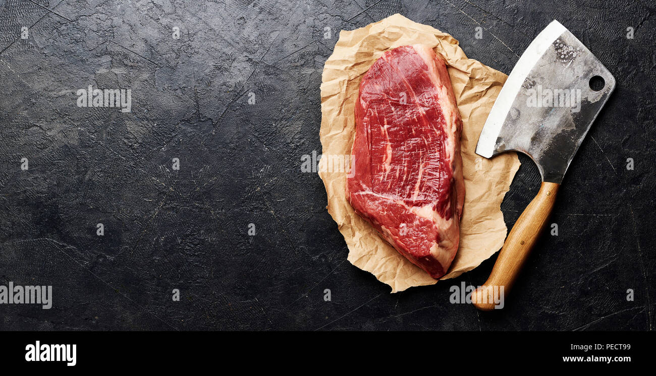 Raw fresh marbled meat Black Angus steak and meat cleaver on brown paper. Meat on black background with copy space. Top view. - Stock Image
