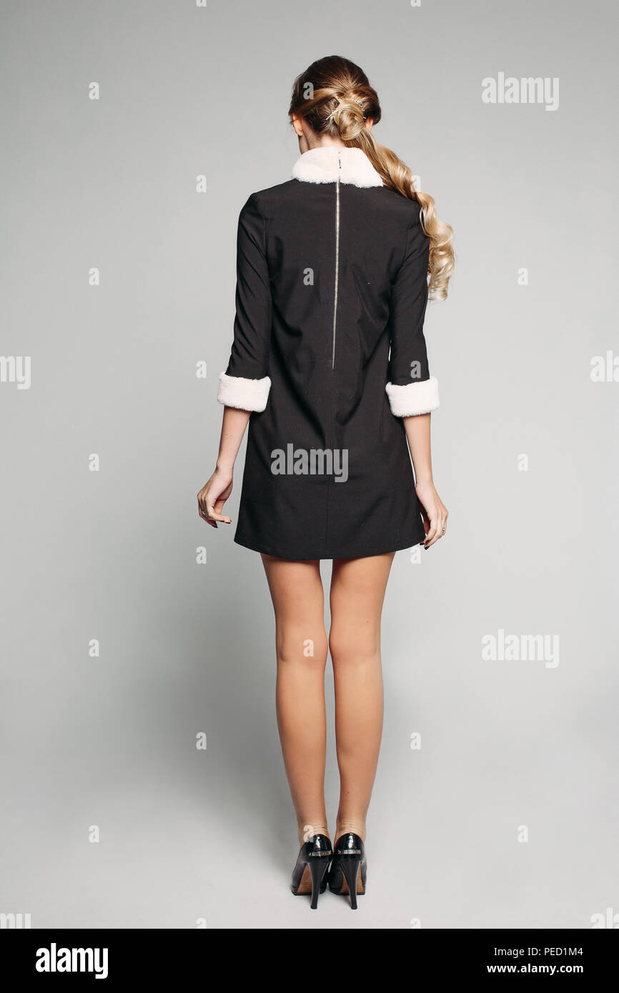 Blonde woman in mini black dress with fur collar and sleeves and high heels. - Stock Image