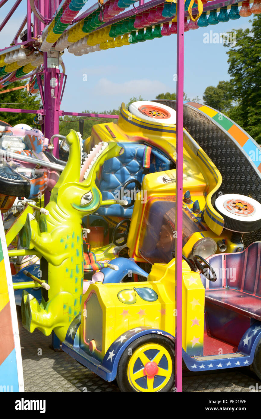 Fun Fair roundabout young childrens ride with alligator and cars being set-up at festival Stock Photo