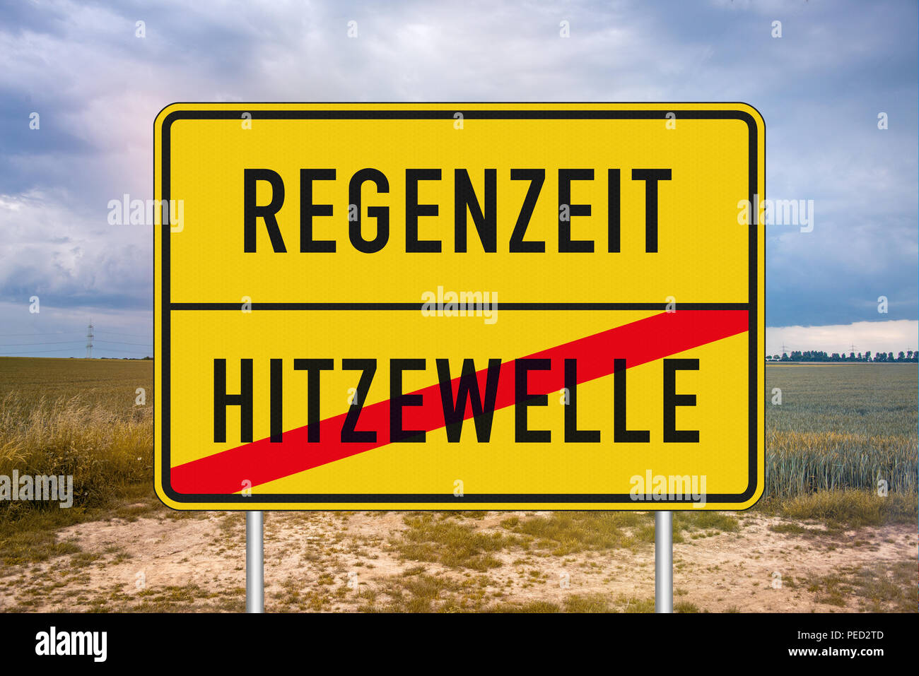 Yellow roadsign or place-name sign with rainy period and heat wave written in german and heat wave being crossed out against cloudy sky and field in b - Stock Image