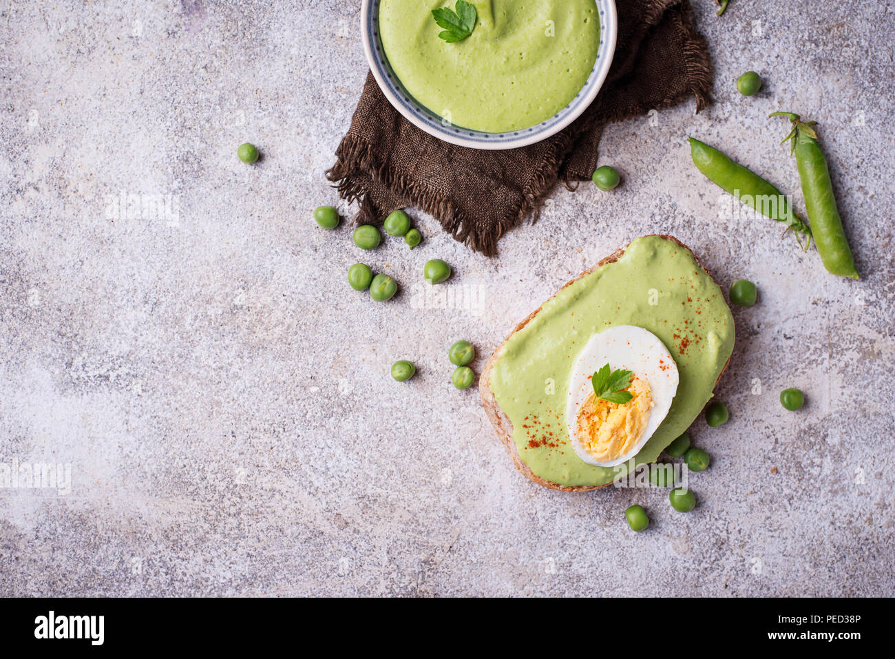Bruschetta with green peas puree and egg - Stock Image