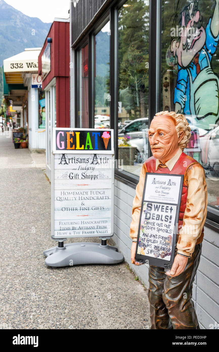 Carved advertising figure outside the Artisans Attic and Fudgery Gift Shoppe in the town of Hope, British Columbia, Canada - Stock Image