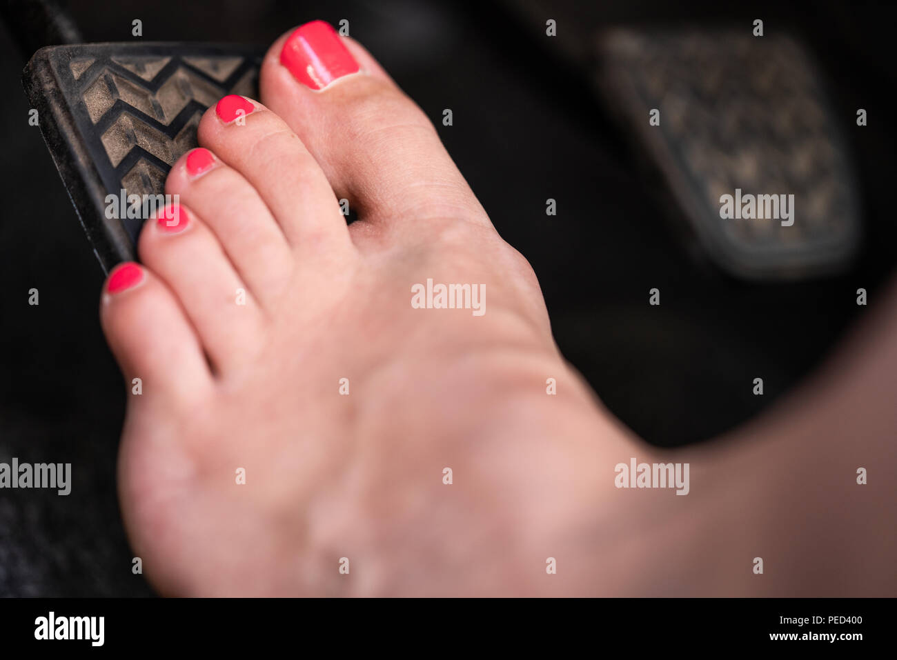A girl is driving her car barefooted. - Stock Image