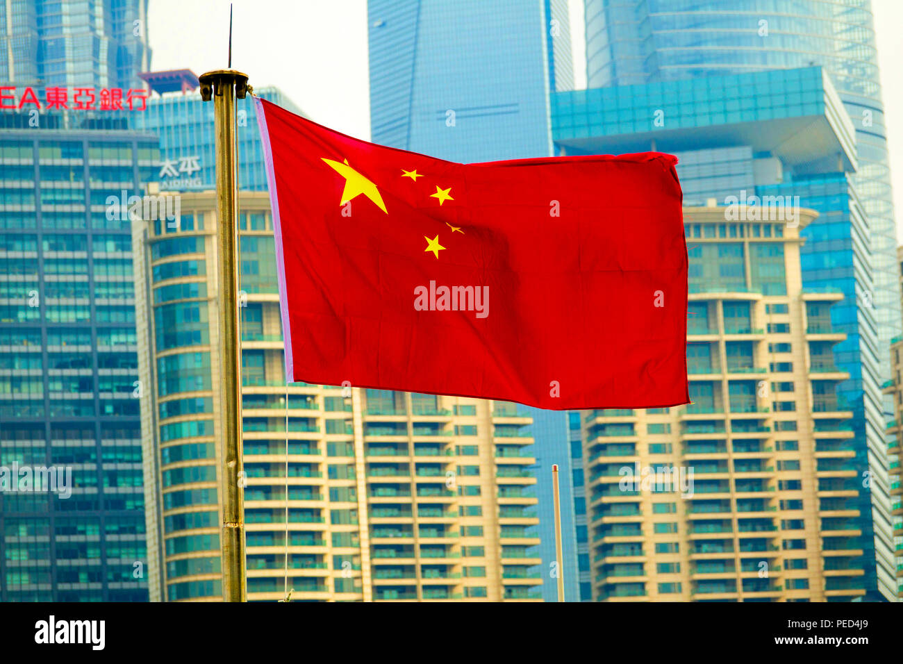 Flag of People's Republic of China in Shanghai Communist Party with Skyline in background - Stock Image