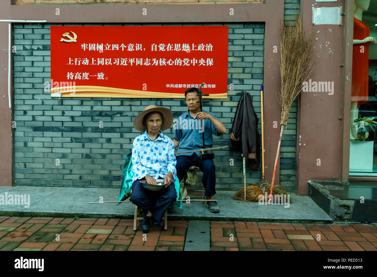 A political sign on the street that promotes Chinese Communist Party Leader Xi Jinping. The sign states that people should follow the leader. - Stock Image