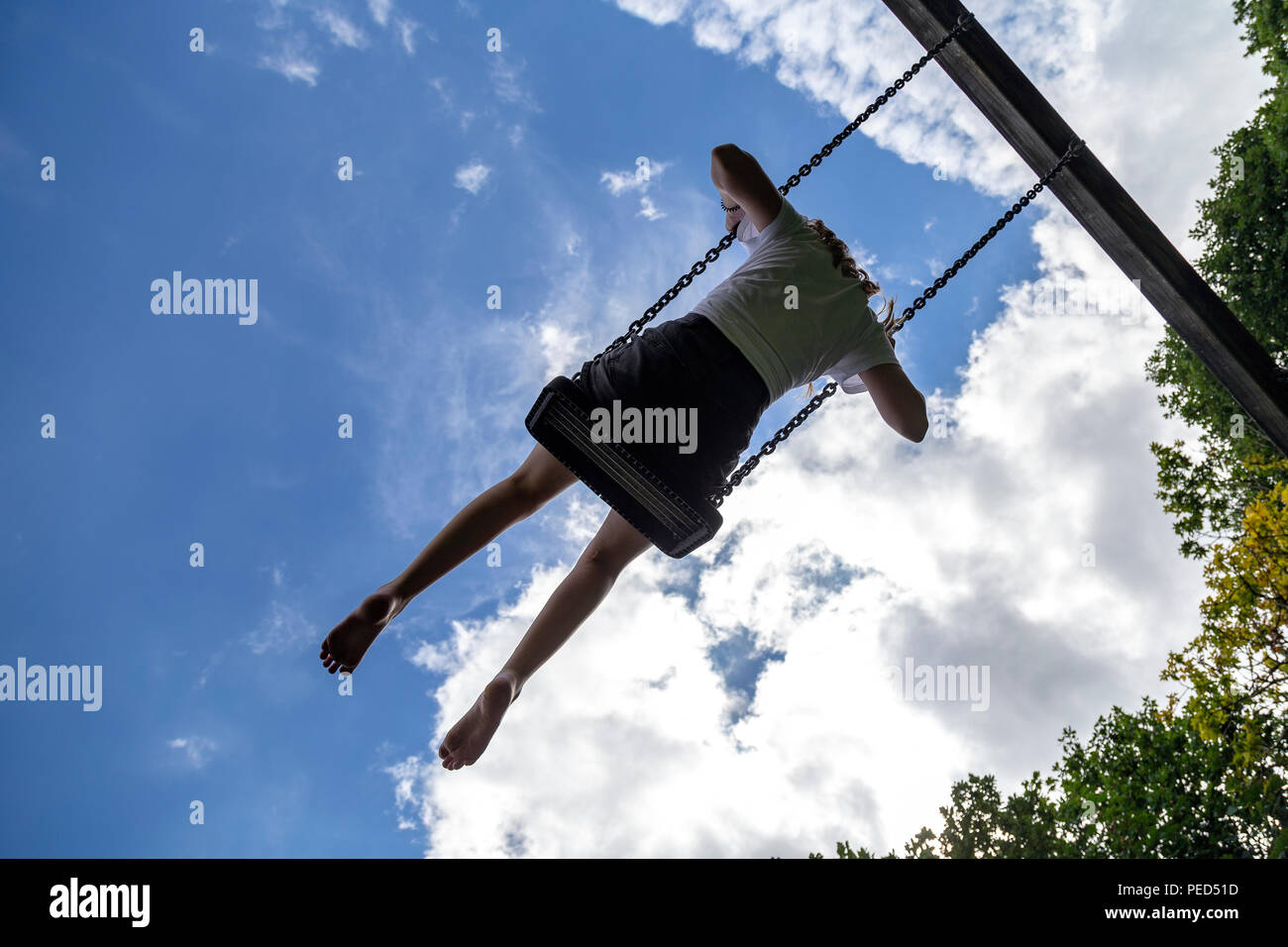 girl on a swing moves back and forth or from side to side while suspended or on an axis,young lady on swing,sway, oscillate, move back and forth, - Stock Image