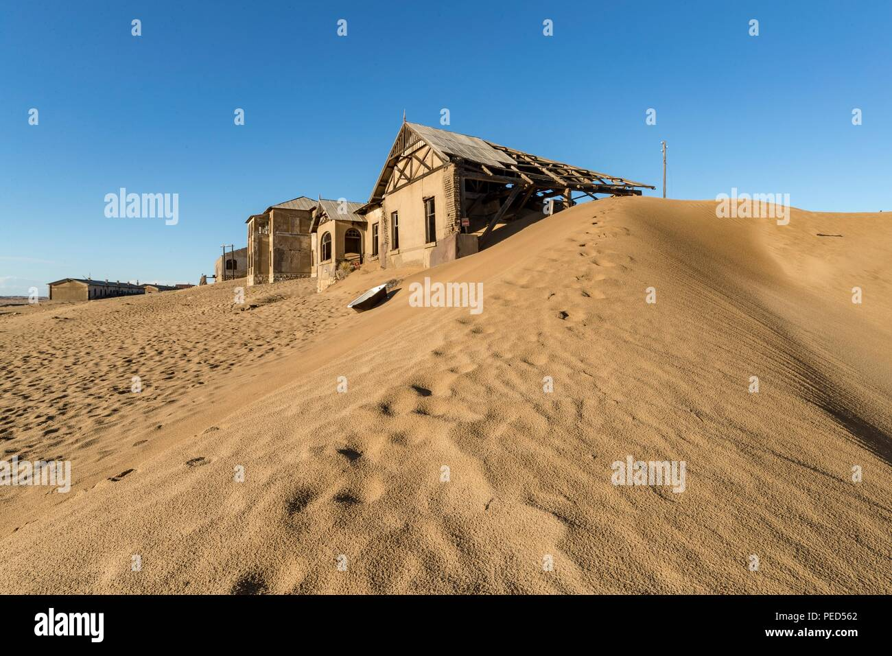 Kolmanskop (Afrikaans for Coleman's head, German: Kolmannskuppe) is a ghost town in the Namib in southern Namibia, 10 kilometres inland from the port  - Stock Image