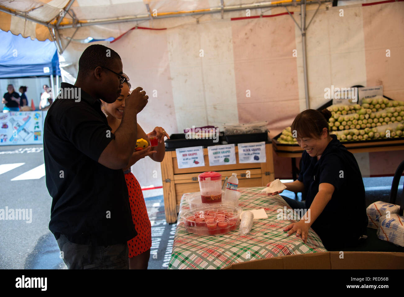 150801-N-UP569-051 NAVAL AIR FACILITY ATSUGI, Japan (August 1, 2015) –  Engineering Aid 2nd Class Jay Murphy and Iaya Murphy try a sample of fresh watermelon and lime juice prepared by a local produce representative Ryoko Kano during Naval Air Facility (NAF) Atsugi's Healthy Lifestyle Festival. The event encourages base residents to develop a healthy lifestyle through exercise and healthy eating. (U.S. Navy photo by Mass Communication Specialist 3rd Class Jason Bawgus/RELEASED) - Stock Image