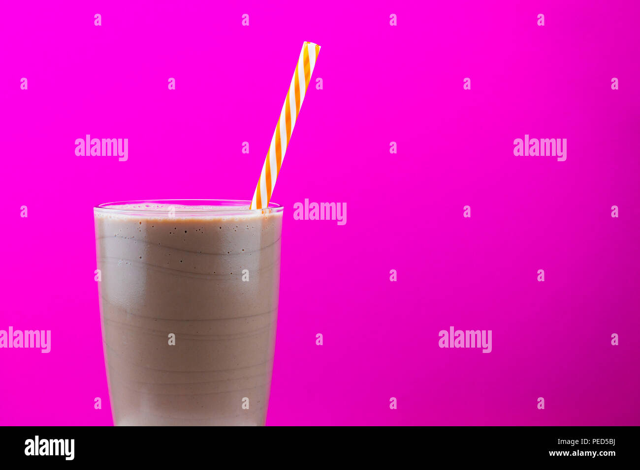 Chocolate milkshake in a glass with a straw against a bright pink background with copy space - Stock Image