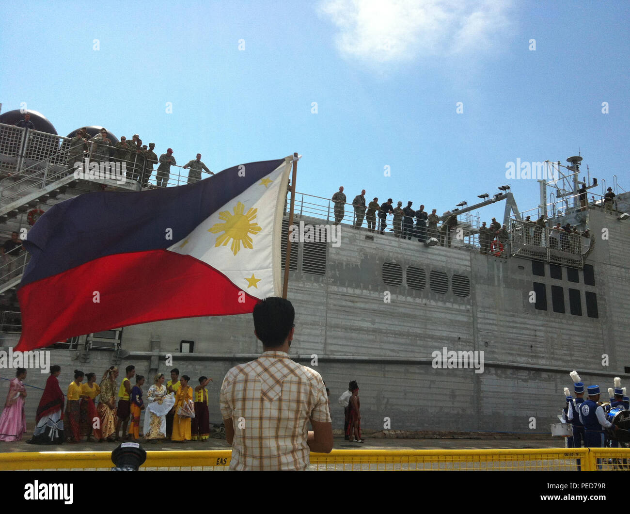 150804-N-ZZ999-029 SAN FERNANDO CITY, Philippines (Aug. 4, 2015) – A man holding the flag of Philippines watches as the Military Sealift Command joint high speed vessel USNS Millinocket (JHSV 3) arrives in San Fernando, Aug. 4. Millinocket is in the Philippines for the fourth stop of Pacific Partnership 2015. Millinocket and embarked Task Force Forager are serving as the secondary platform for Pacific Partnership, led by an expeditionary command element from the Navy's 30th Naval Construction Regiment (30 NCR) from Port Hueneme, Calif. Now in its 10th iteration, Pacific Partnership is the larg - Stock Image