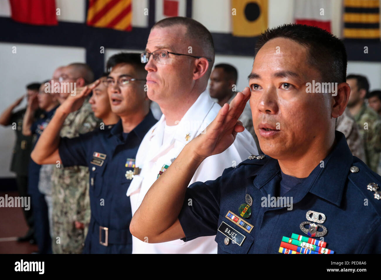150806-M-GO800-040 SAN FERNANDO CITY, Philippines (August 6, 2015) – Philippine service members salute and U.S. service members stand at attention while the Philippine national anthem plays during an opening ceremony Aug. 6. Task Force Forager will be in the Philippines until Aug. 15 providing medical and engineering assistance. Task Force Forager, embarked aboard the Military Sealift Command joint high speed vessel USNS Millinocket (JHSV 3) is serving as the secondary platform for Pacific Partnership, led by an expeditionary command element from the Navy's 30th Naval Construction Regiment (30 - Stock Image