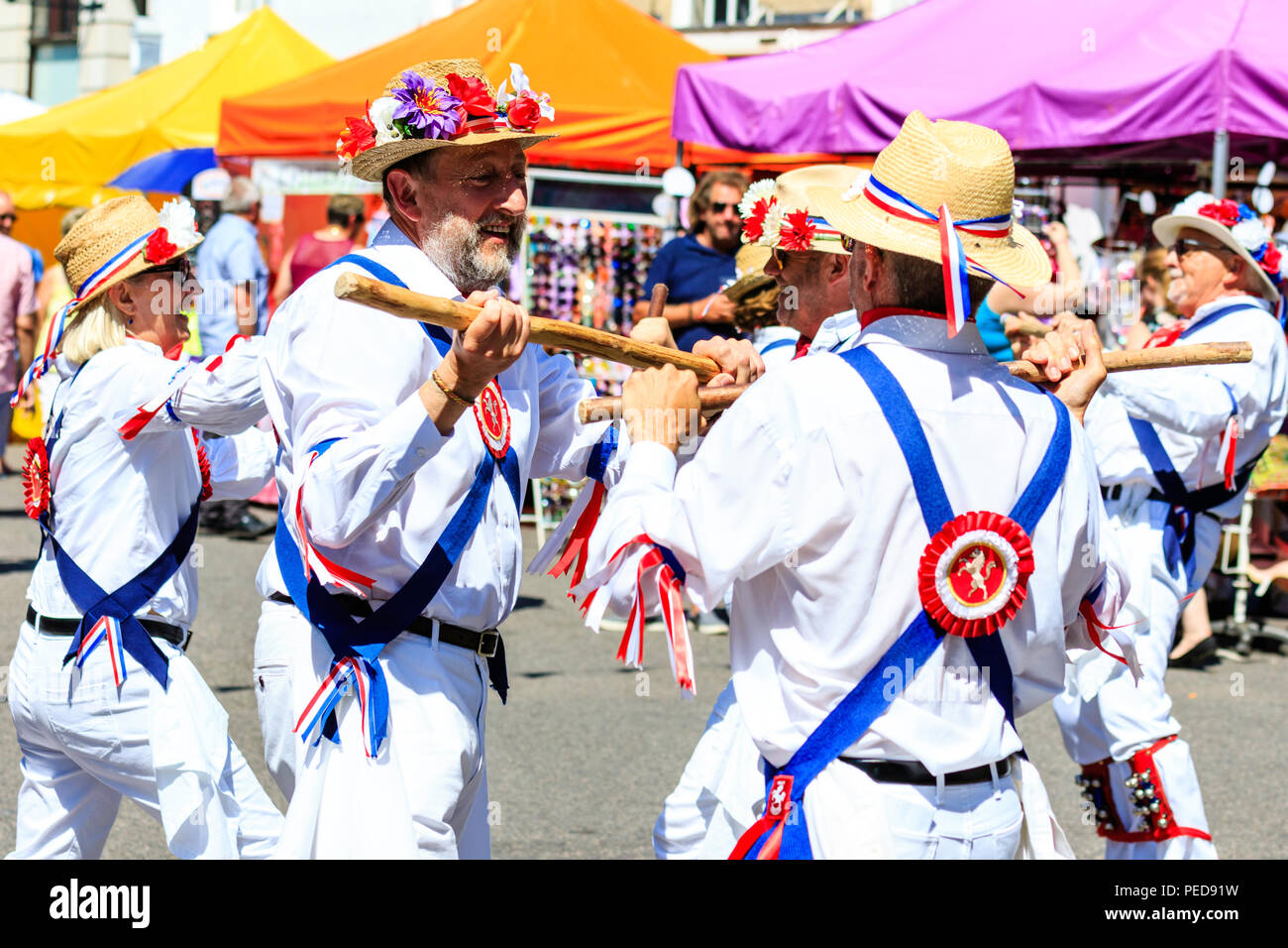 Traditional English folk dancers from the East Kent Morris side dancing in the street on a hot summer day during the Sandwich Folk and Ale Festival - Stock Image
