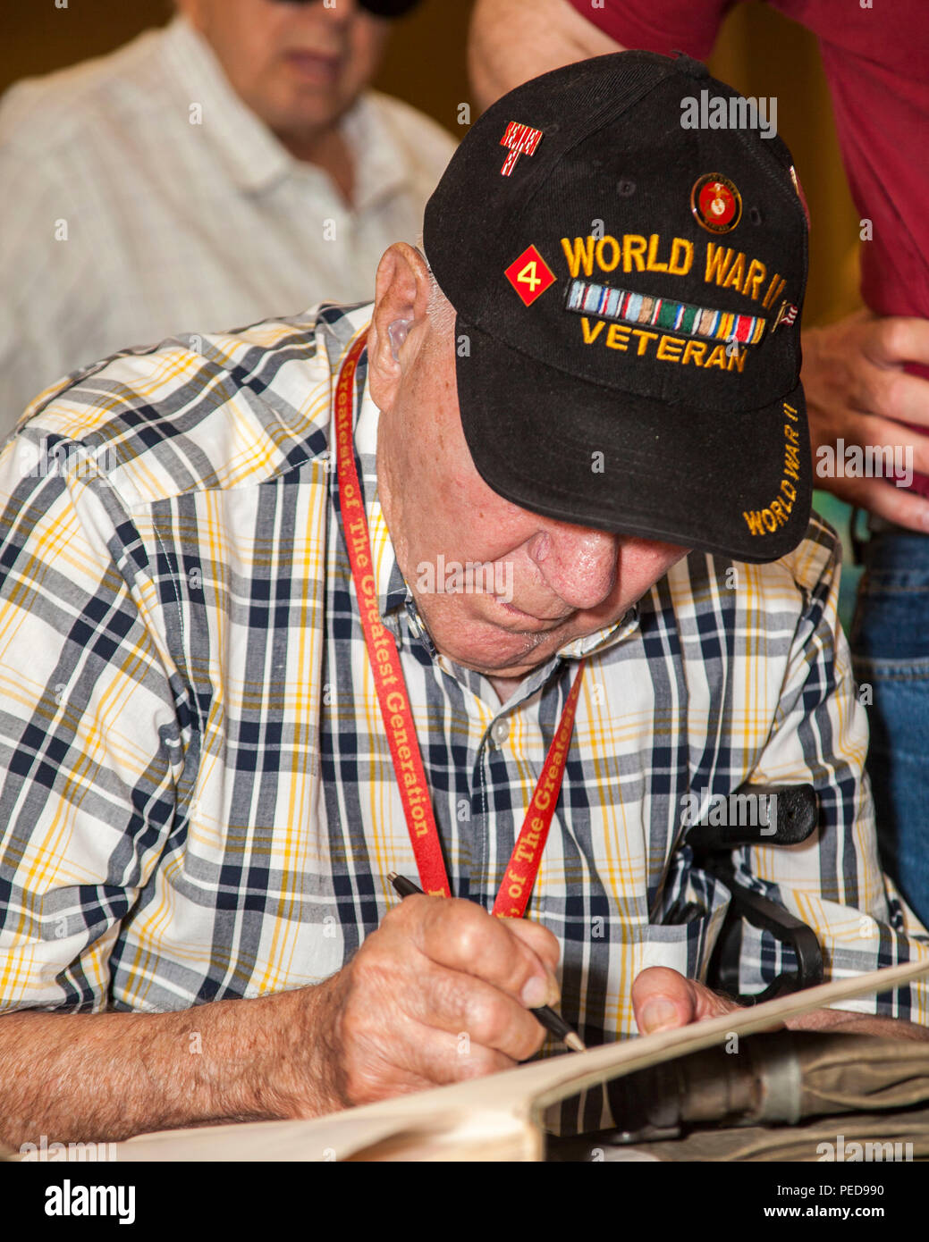A veteran of 4th Marine Division (4th MARDIV) writes his name in a