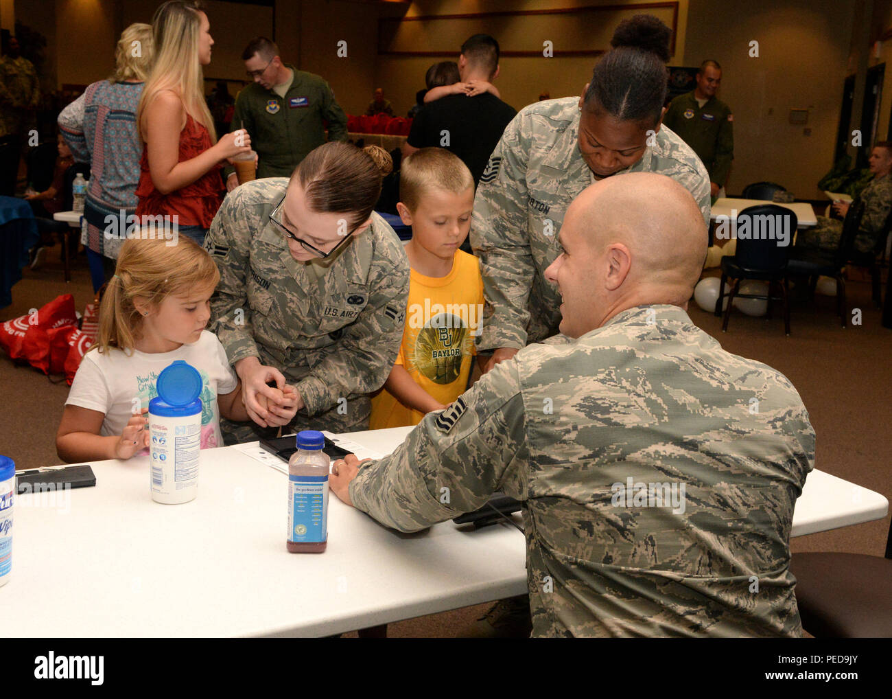 U.S. Air Force Tech. Sgt. Joshua Leach, Tech. Sgt. Kristy Horton, and Airman 1st Class Allie Harrison, 97th Security Forces Squadron members, fingerprint children during Operation Deploying Family at the Freedom Community Center, Aug. 5, 2015. Once finalized, the identification cards were provided to the children's parents for safe keeping. (U.S. Air Force photo by Airman 1st Class Megan E. Acs/Released) - Stock Image
