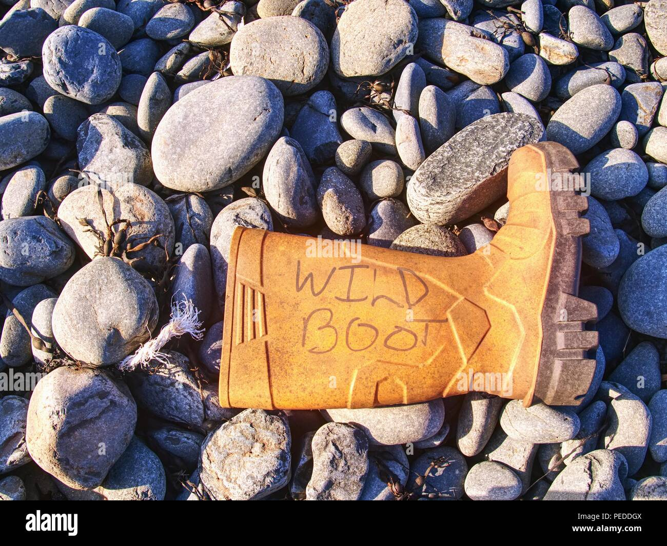 Dangerous rubbish on a stony beach.  Photo showing pollution problem. Dangerous garbage ejected from the sea on remote beaches. - Stock Image